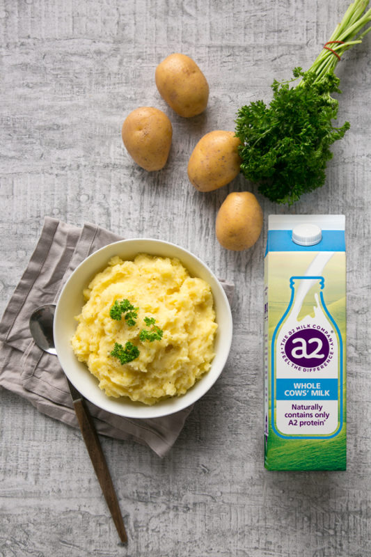 potato mash topped with parsley in a white bowl over a grey napkin and serving spoon, potatoes, freesh parsley and a2 milk carton next to the bowl