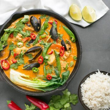 Thai Red Fish Curry in cast iron skillet, next to a white cloth with fresh ginger root, cilantro, red chili peppers and halved limes, and a small bowl of rice.