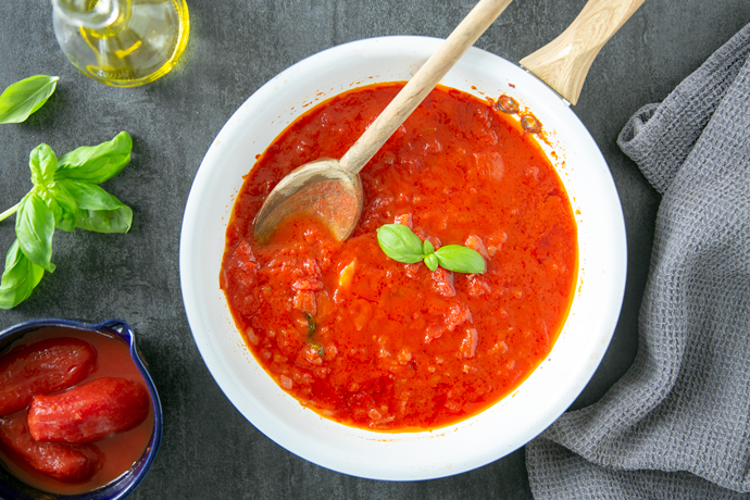 italian tomato sauce in a white pan, next to a grey napkin on the right side, on the left side a small bowl with canned tomatoes, basil leaves and a small glass bottle of extra-virgin olive oil.