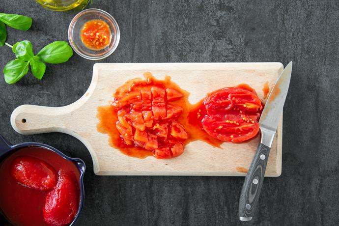 tomate picado e tomate cortados ao meio com uma faca em uma tábua de madeira, no lado esquerdo de conservas de tomate em uma tigela azul e nas folhas de manjericão do lado superior esquerdo e em uma tigela pequena com as sementes removidas dos tomates.