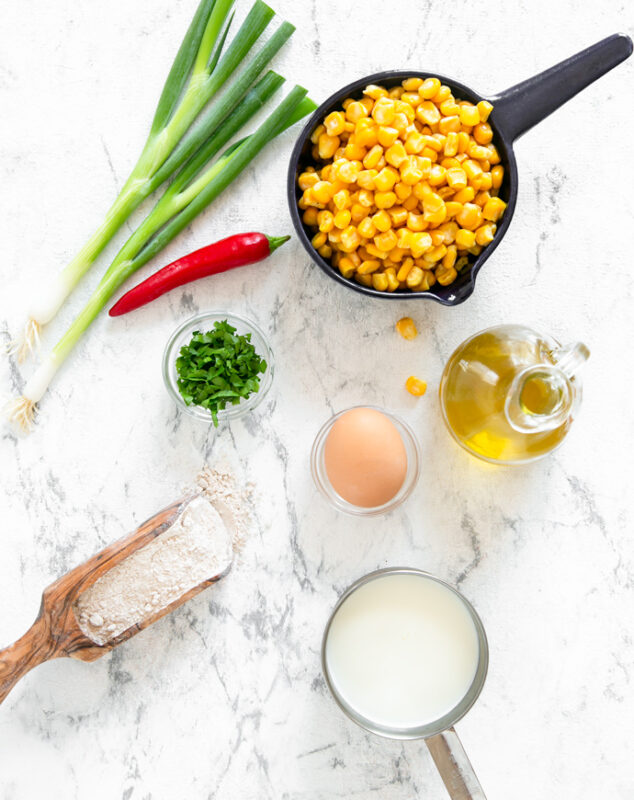 spring onions, red chili pepper, cup with sweetcorn, olive oil in glass bottle, egg in a small cup, milk in a small cup, wood scooper with flour, and cilantro in a small cup