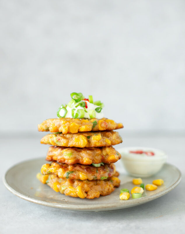 grey plate with a tower of sweetcorn fritter topped with yogurt dip, chopped spring onions and chilli pepper, small bowl of yogurt dip on the side.