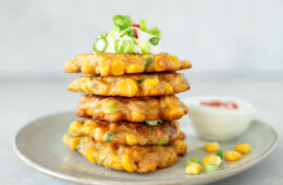 grey plate with a tower of sweetcorn fritter topped with yogurt dip, chopped spring onions and chilli pepper, small bowl of yogurt dip on the side