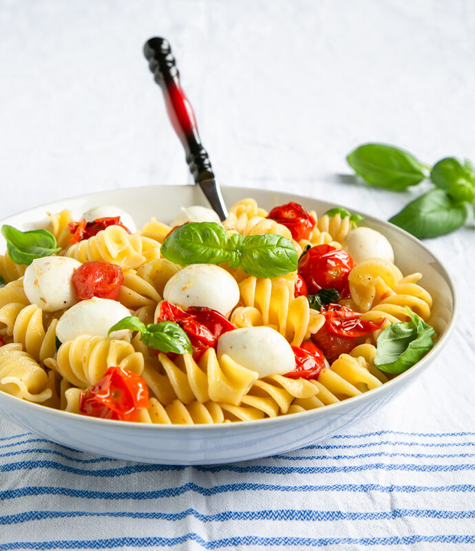 Italian caprese pasta in a large white bowl with a serving spoon, basil leaves in the background