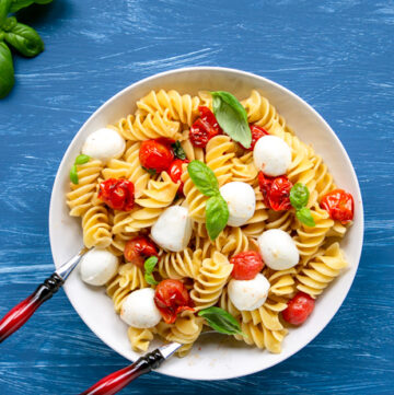 Italian caprese pasta salad in a large plate with serving spoons, basil leaves scattered over the blue background