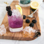 bramble cocktail topped with a slice of lemon and two blackberries secured in a skewer.
