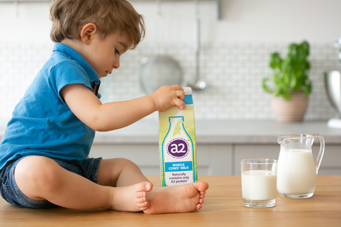 toddler holding carton of a2 milk, next to glass and jug full of milk, kitchen in the background