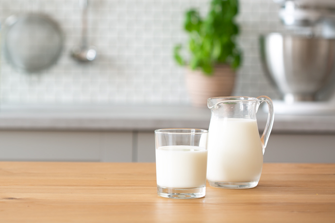 glass full of milk and jug full of milk on wood kitchen counter, kitchen in the background