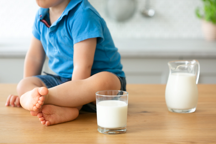 toddler next to a glass of milk, jug of milk on the right side, kitchen in the background