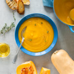 bowl of creamy butternut squash soup served with grilled bread, next to a pot with more soup, butternut squash slices,thyme sprigs, and small pot of olive oil