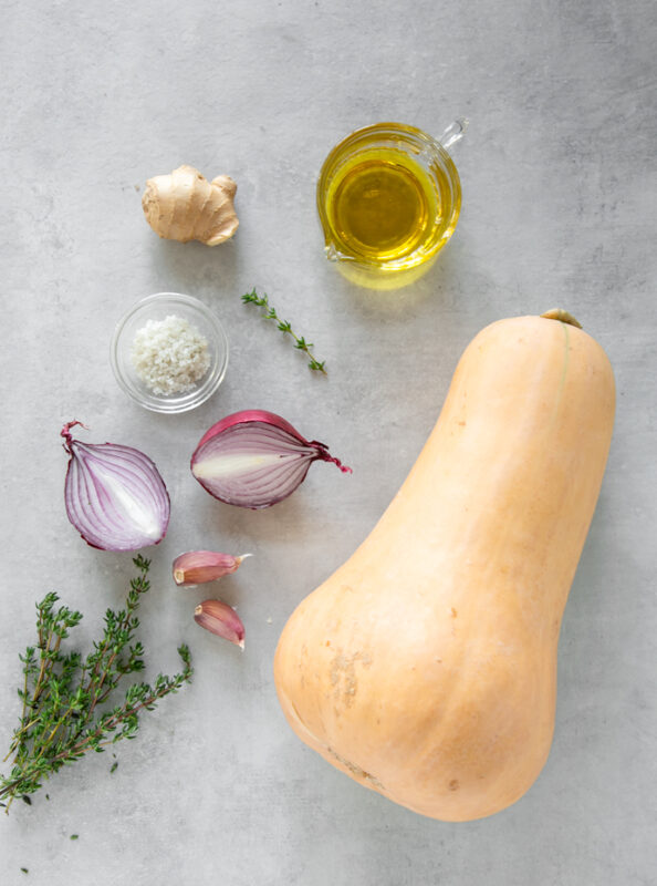 fresh thyme sprigs, 2 garlic cloves, red onion halved, sea salt in a small bowl, piece of fresh ginger, small jug with olive oil and a large butternut squash