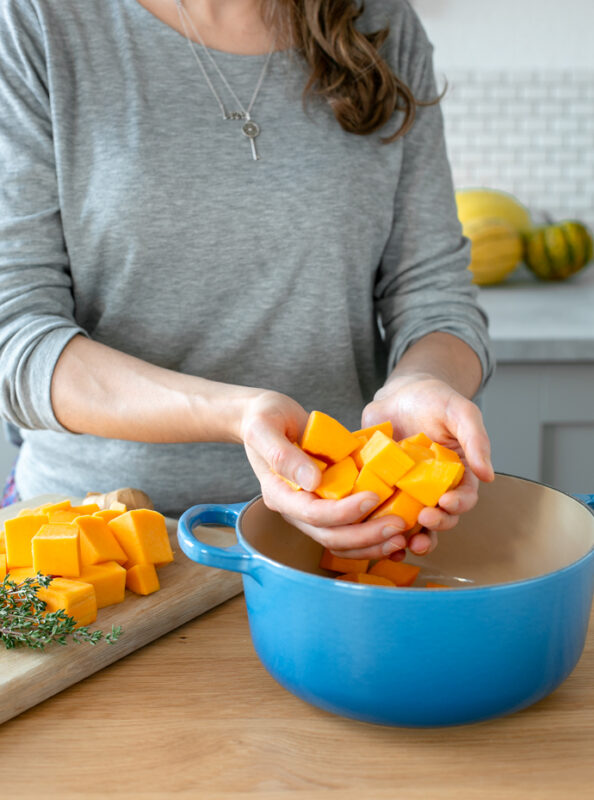 andrea holding chopped butternut squash over a cast iron pot, next to the lady butternut squash chunks over a wood board