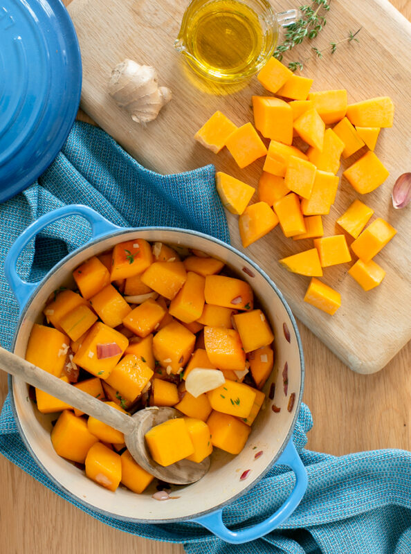 butternut squash soup recipe step 1: sauteed vegetables in a large cast iron pot, next to a wood board topped with butternut squash chunks, thyme sprigs, garlic, ginger piece and small just with olive oil