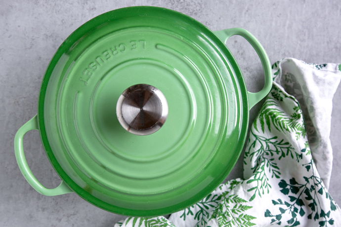 green cast iron pot with lid on top of it, next to a white and green kitchen cloth