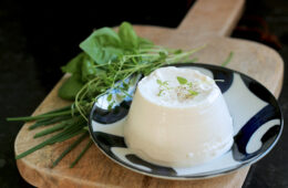 homemade ricotta over a small white an blue plate, next to fresh aromatic herbs, both over a wood board,