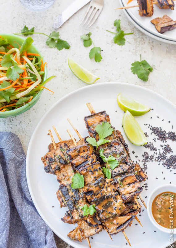 grilled eggplant kebabs served on a dish with lime wedges and tahini marinade.