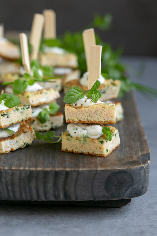 individual frittata sandwhich bites topped with fresh herbs on a wood board