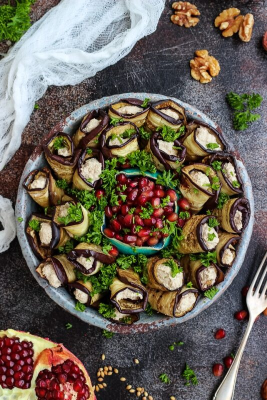 eggplant roll ups on a plate served with pomegranate