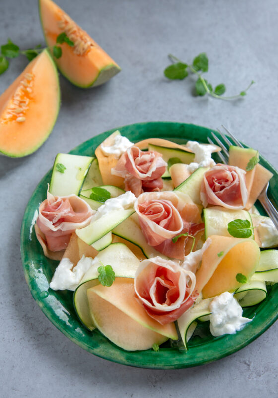 recipe from 20-minute italian cookbook: melon, zucchini, prosciutto and burrata salad on a green plate, two slices of melon in the background and fresh oragano leaves