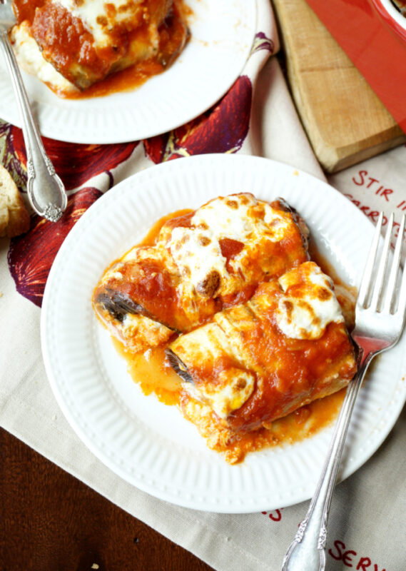 cheesy eggplant rollatini on a white plate.