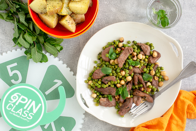 Air Fryer Mint Lamb with Toasted Hazelnut and Peas, served with roasted potatoes on the side, and spin class gear of goodness next to the dish