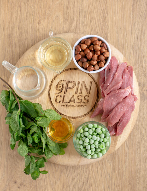 woodboard with fresh mint leaves, hazelnut oil in a small pot, frozen peas in a small pot, strips of lamb meat, hazelnuts in a small pot, white wine in a small pot, and water in a small jug