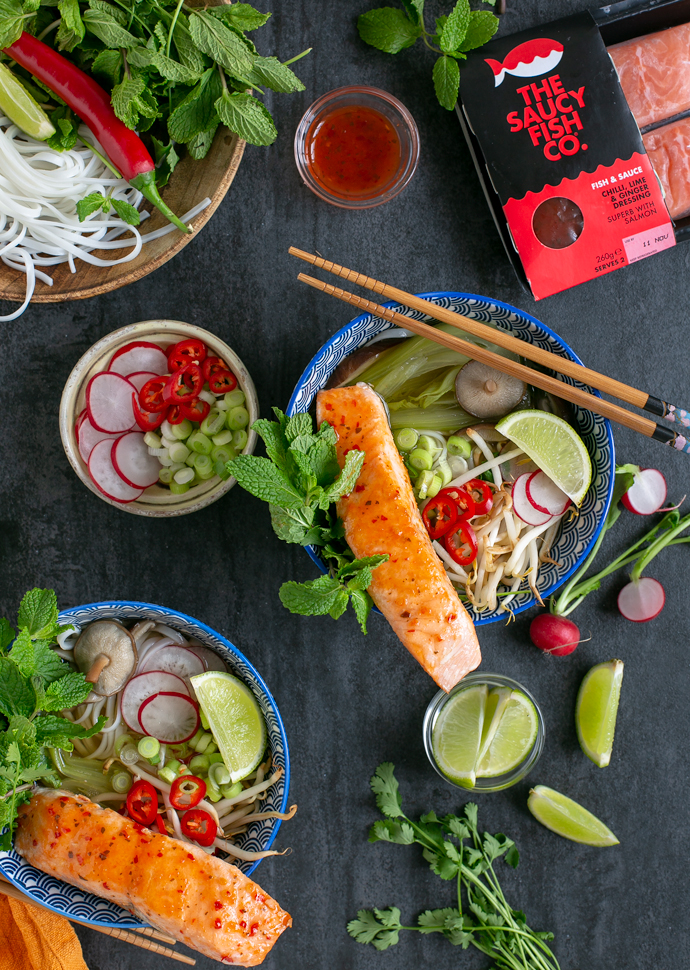salmon pho served in two large bowls, toppings in small pot next to the bowls, package of the saucy fish co salmon fillets on the top right side of the image.