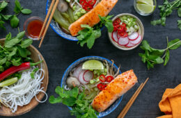 salmon pho served in two large bowls, toppings in small pot next to the bowls