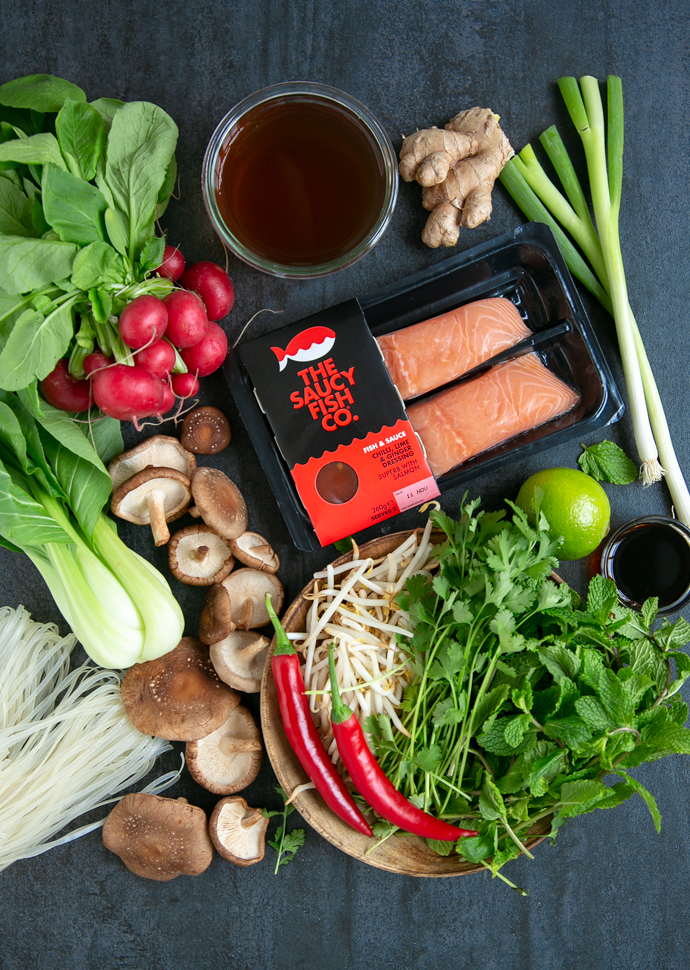 ingredients for the salmon pho from the top right side: ginger, broth, the saucy fish co salmon fillets, spring onions, lime, soy sauce, fresh mint leaves, fresh cilantro, bean sprouts, red chilli, shiitake mushrooms, rice noodles, pak choi and radishes.
