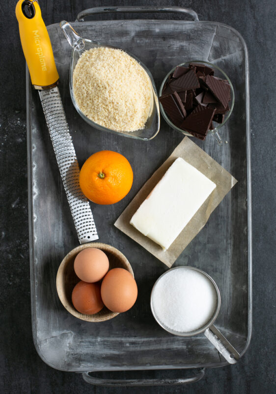 caprese cake ingredients: almond flour, chunks of dark chocolate, butter, sugar, eggs, orange zest