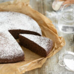 italian water cake with a slice of cake in evidence, water jug cookies cutters and sugar in a sieve on the side