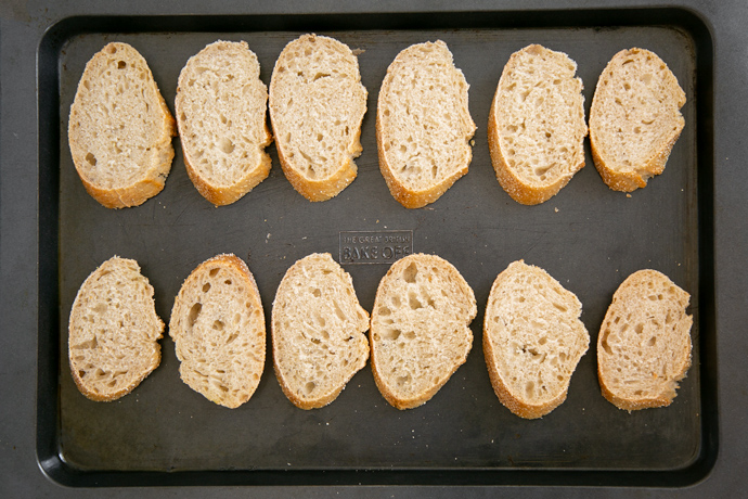 recipe step 1: sliced bread on a baking tray ready to be baked until dry and crunchy.