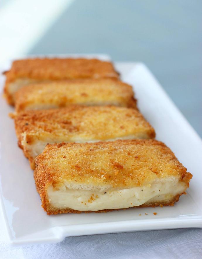 three halfed mozzarella in carrozza showing the molten cheese filling..
