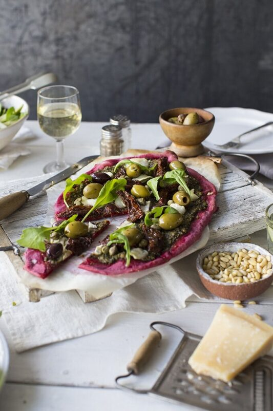Beet Pizza with Beet Leaf Pesto, topped with capers, olives and sun dried tomatoes for loads of flavour. Shown on a table set for two with wine and salad.
