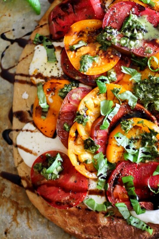 Almond flour pizza base topped with tomatoes, mozzarella and chimichurri sauce