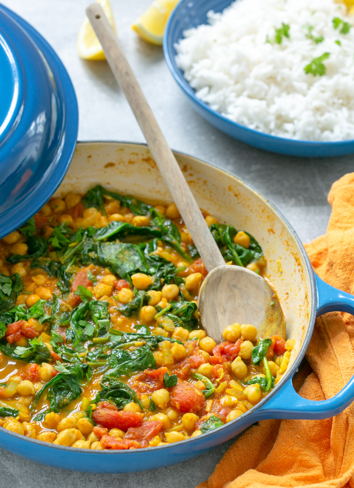 spinach and chickpea curry in a large pot, served with rice on the side