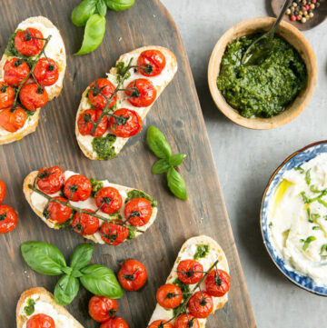 Cherry tomato confit bruschetta with ricotta and basil pesto over wood board, served with ricotta and pesto on the side.