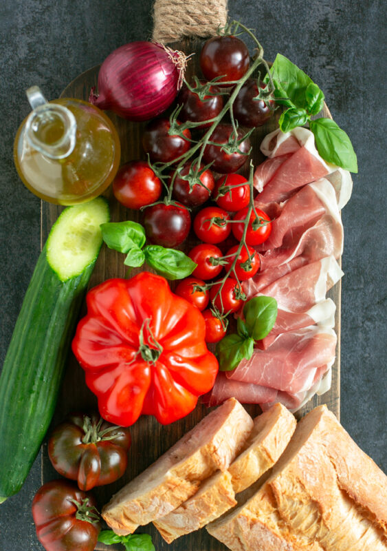 recipe ingredients: bottle of olive oi, red onion, tomatoes on the vine, heirloom tomato, cucumber, bread slices, parma ham slices and basil leaves on a wood board