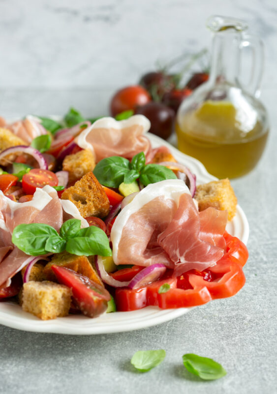 panzanella salad with parma ham on a serving dish, bottle of olive oil and tomatoes in the background