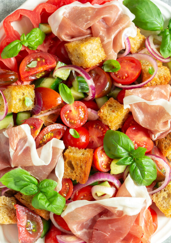 close up of panzanella salad with parma ham, bread cubes, tomatoes, onion, cucumber and basil leaves