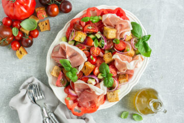panzanella salad with parma ham on a serving dish, next to mixed tomatoes, bottle of olive oil and napkin with fork and spoon over it