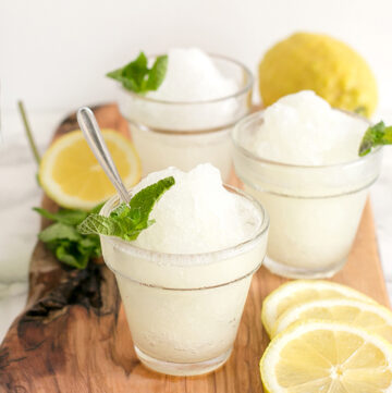 three glasses with lemon granita, topped with mint leaves