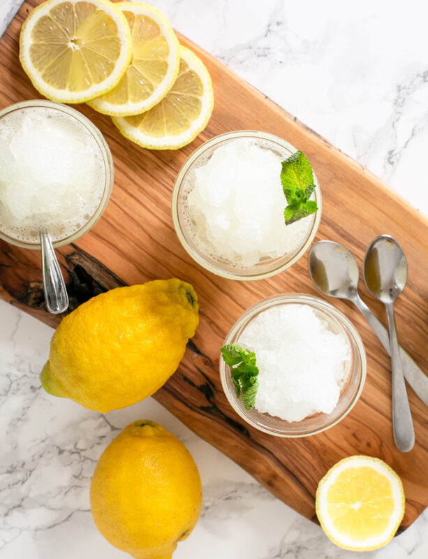 three glasses with lemon granita topped with mint leaves, two lemons, slices of lemon and spoons.