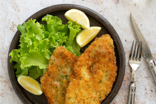 breaded chicken cutlets on a plate with lemon wedges and salad