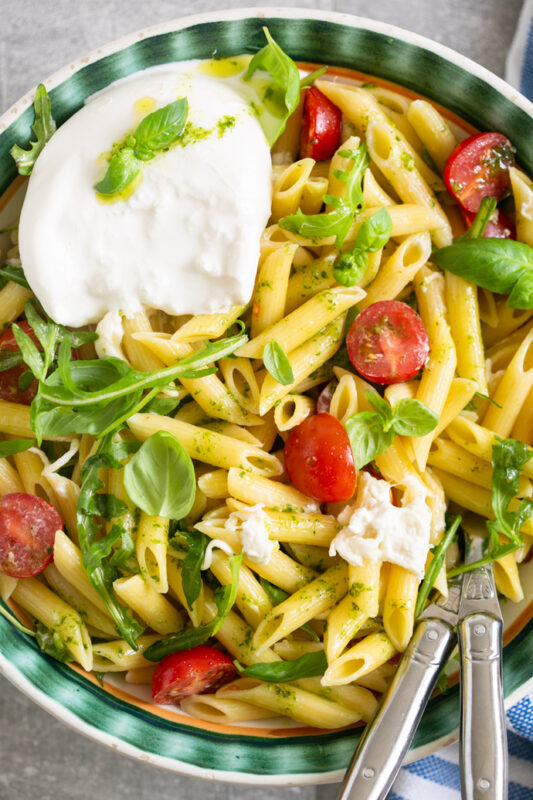 burrata pasta salad served in a big bowl with serving spoons.
