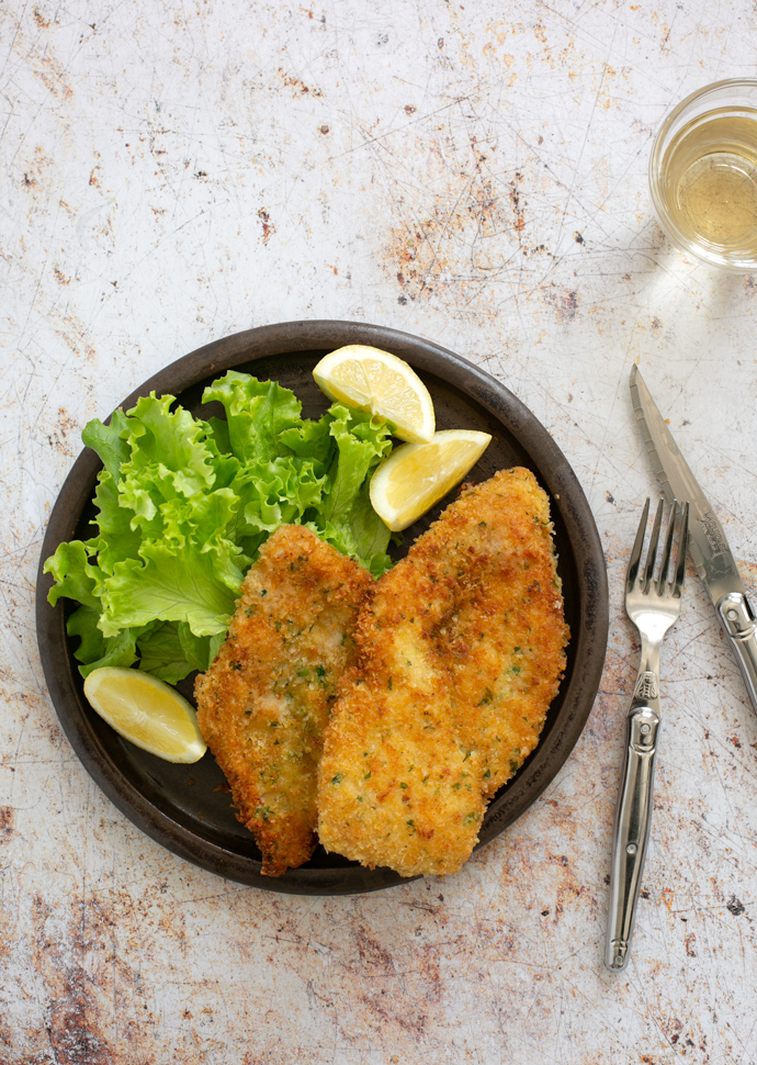 italian breaded chicken cutlets on a plate with lemon wedges and salad