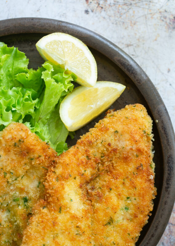 breaded chicken cutlets on a plate with lemon wedges and salad leaves