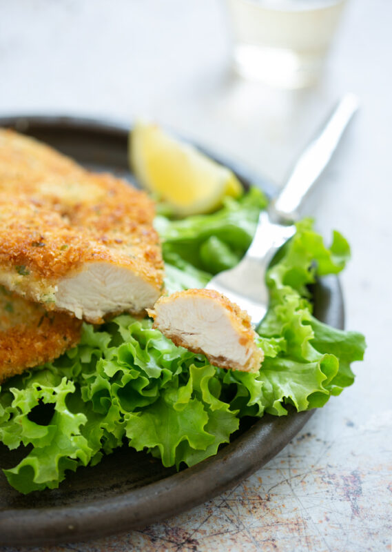 chicken cutlets on a plate, fork holding a small piece of the cutlet