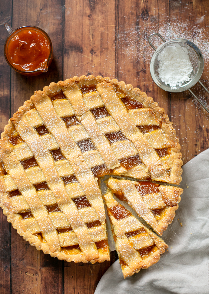 italian jam tart with 2 slices cut ready to be served. Confectioner sugar and peach jam on the side.