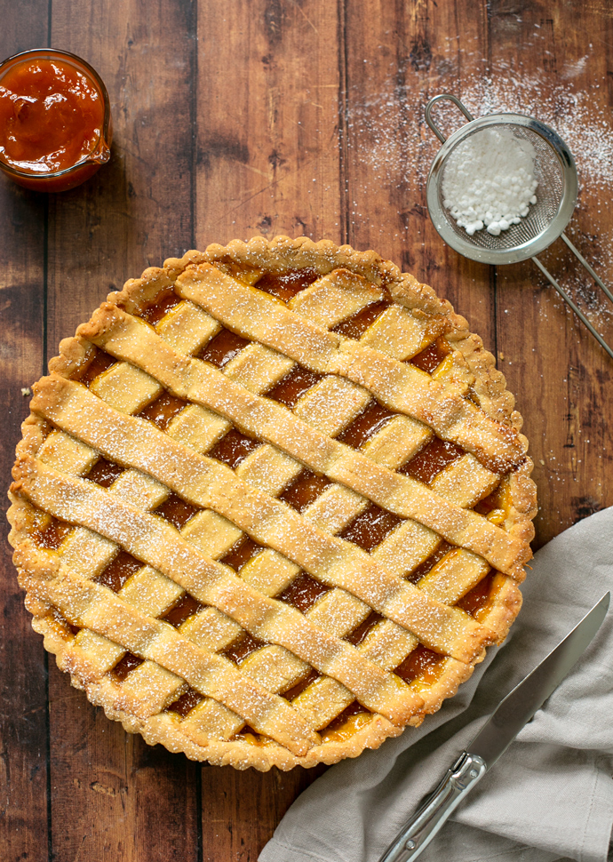 crostata with jam with confectioner sugar and peach jam on the side.